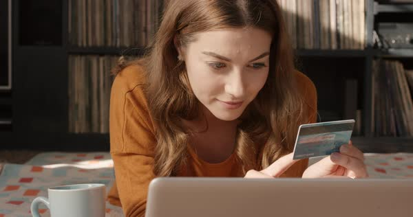 Beautiful woman shopping online with credit card and laptop at home in trendy loft apartment happy with purchase vintage records in background orange retro colours and styling Royalty-free stock video