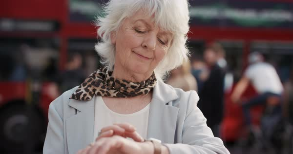 Portrait of happy mature old woman in city using smart watch sharing social media connection technology, slow motion Royalty-free stock video