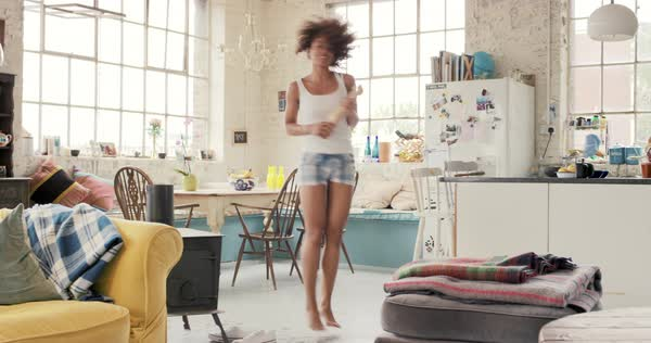 Happy curly haired young woman dancing in kitchen wildly hair bouncing wearing pyjamas at home photos on fridge Royalty-free stock video