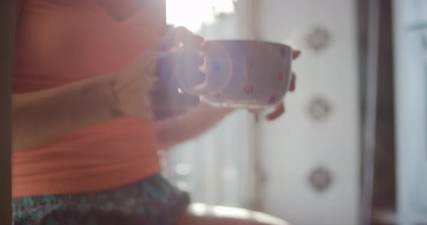 Beautiful young woman drinking coffee alone at home looking out of window Royalty-free stock video