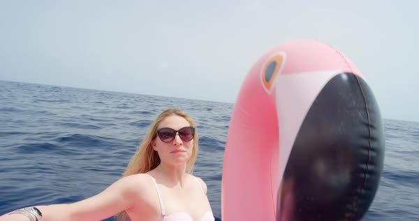 Woman lying on inflatable flamingo floating in middle of ocean girl relaxing in summer sunshine enjoying tropical vacation Royalty-free stock video