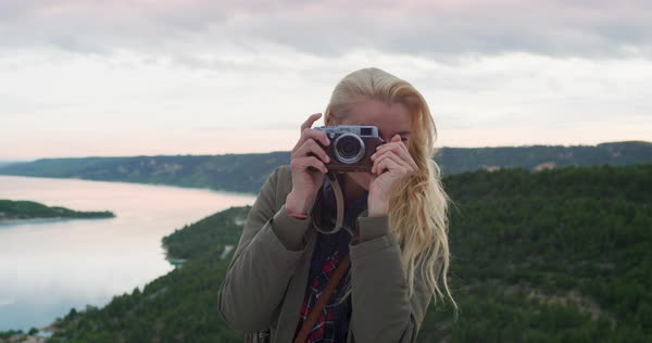 Woman taking photograph with retro styled digital camera photographing scenic landscape nature background view enjoying vacation travel  Royalty-free stock video