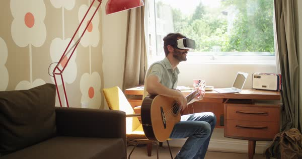 Young man wearing virtual reality headset learning to play guitar instrument at home watching 360 video in retro styled modern apartment Royalty-free stock video