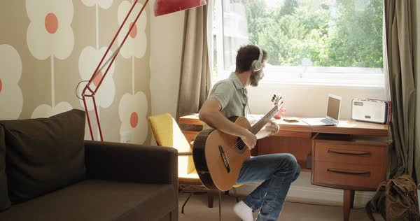 Man sitting at window learning to play guitar using laptop computer at home in retro styled trendy apartment Royalty-free stock video