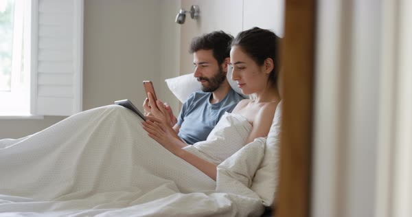 Young couple lying in bed using smartphone digital tablet technology scrolling online browsing sharing real moment in morning Royalty-free stock video