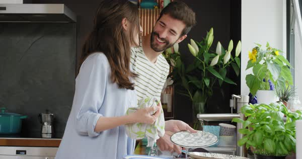 Couple washing dishes dancing at home wearing pajamas having fun laughing Royalty-free stock video