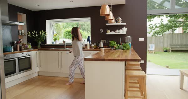 Woman dancing in kitchen wearing pajamas in the morning listening to music Royalty-free stock video