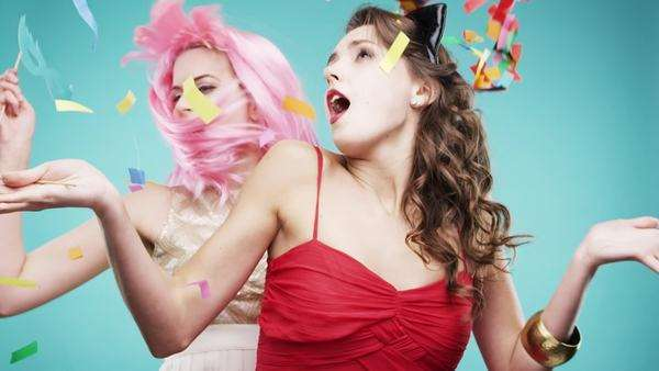 Two girlfriends dancing wearing red dress and pink hair in slow motion party photo booth Royalty-free stock video