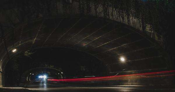 Long exposure street level view of traffic passing by creating fast paced light streaks under a bridge in Central park, New York. Royalty-free stock video