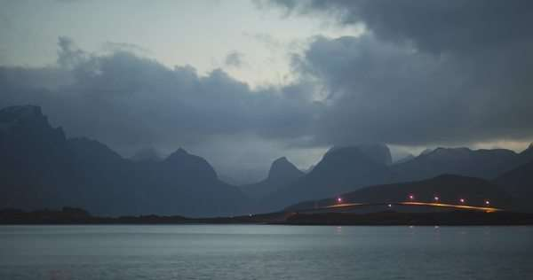 Day to night timelapse view of cars driving over a bridge with a mountain backdrop, Ramberg, Flakstadoya, Lofoten islands, Norway Royalty-free stock video