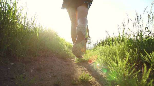Close-up shoot of runners feet running into sun in slow motion Royalty-free stock video