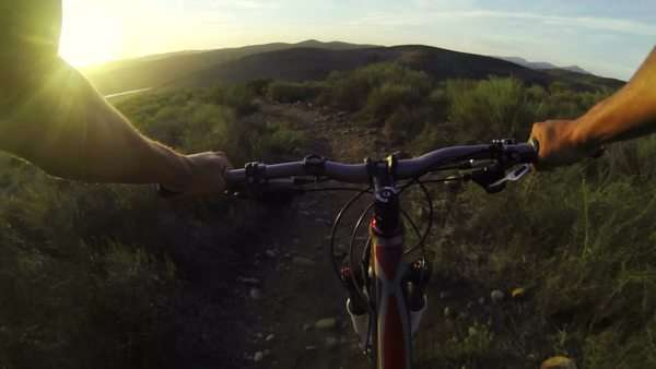 Point of view of man mountain biking down a hill at sunset Royalty-free stock video