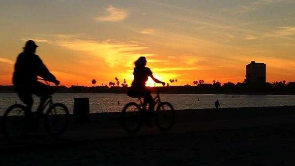 silhouetted Couple Riding Bikes At Sunset Royalty-free stock video