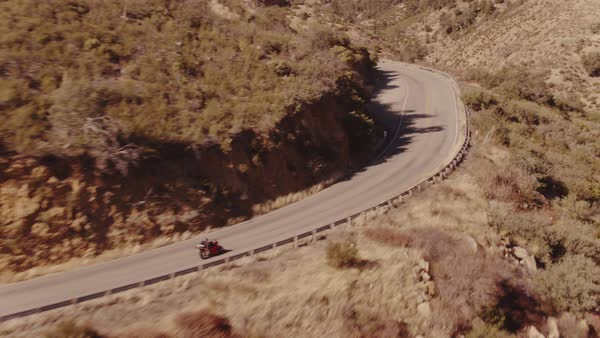 Aerial shot of extreme motorcyclist racing on curvy mountain road  Royalty-free stock video