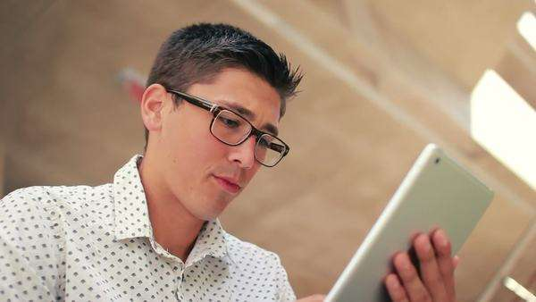 Young Hipster Male Student Using Tablet PC At School While Studying Royalty-free stock video