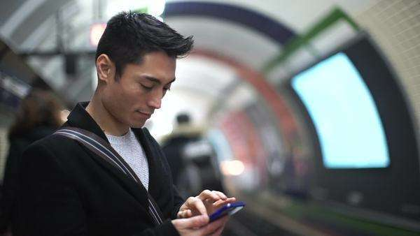 Young Asian man types on his phone as a subway train arrives Royalty-free stock video