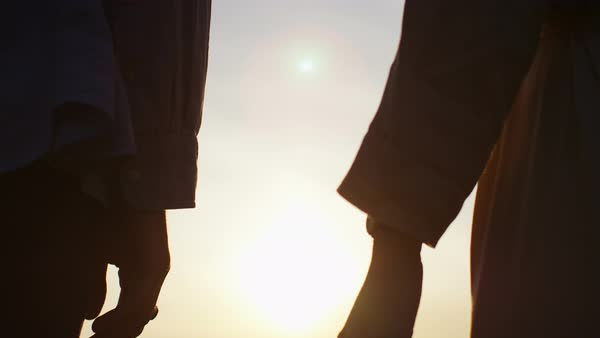 Silhouette hands of a couple come together at sunset Royalty-free stock video