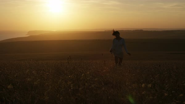 Young woman runs with her teddy bear in a field with the sunset behind her, in slow motion Royalty-free stock video