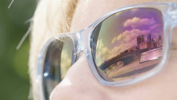 Reflection in woman's sunglasses of London Bridge and the city during a sunny day Royalty-free stock video