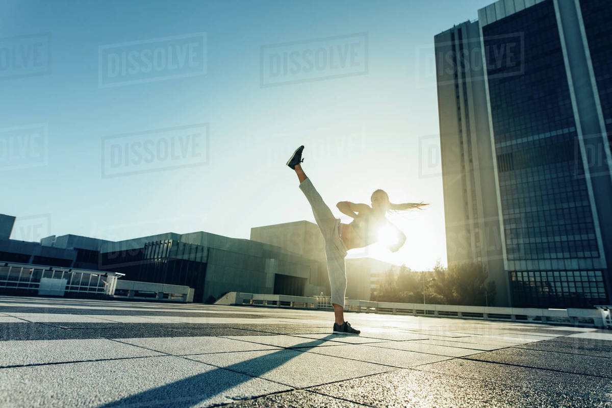 Urban woman doing high roundhouse kick outdoors in the city. Female practicing martial arts in a sunny day. Royalty-free stock photo