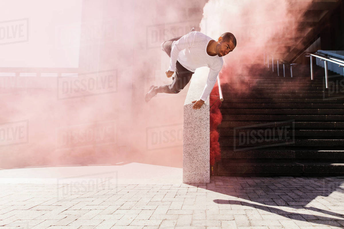 Man practices parkour and free running with smoke grenade. Young male practicing parkour in urban space. Royalty-free stock photo