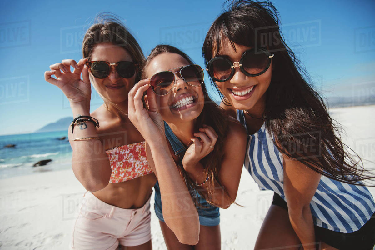 b3d44b8fa7 Portrait of playful beautiful young women in sunglasses on the beach. Female  friends with sunglasses looking at camera and smiling.