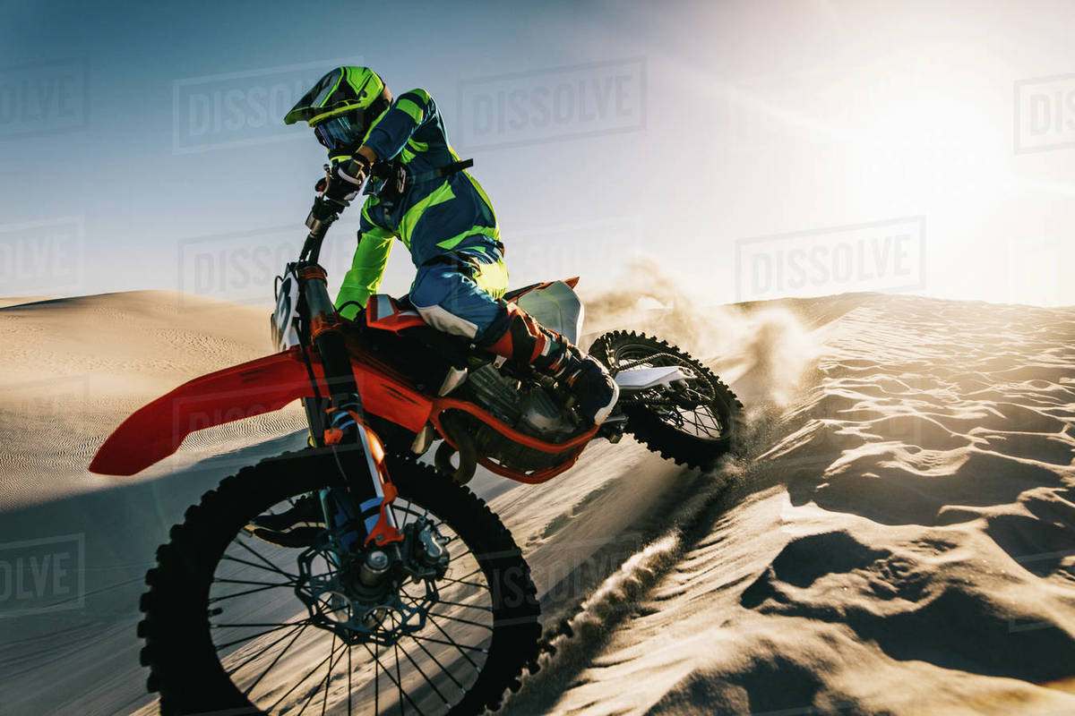 Man driving dirt bike over sand dunes in desert. Dirt biker turning and going down from sand dune. Royalty-free stock photo