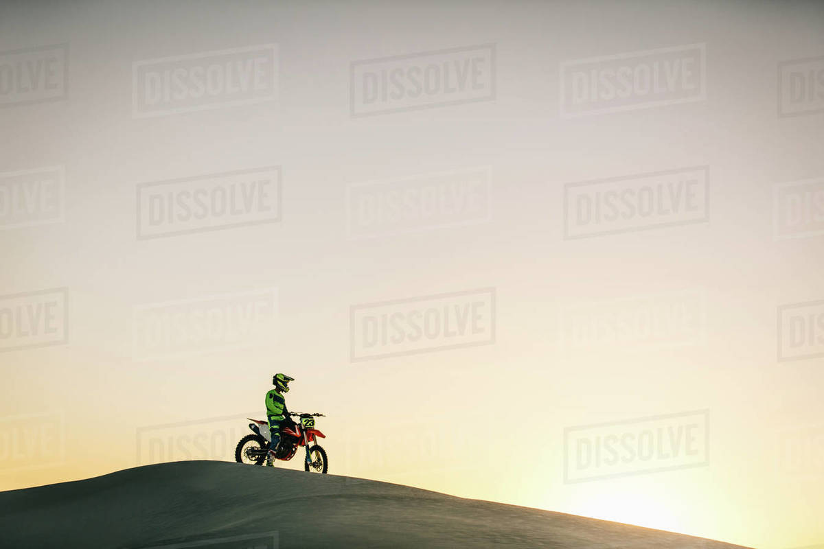 Motocross rider sitting on his bike on a sand dune. Motorcycle rider driving on the dunes during sunset. Royalty-free stock photo