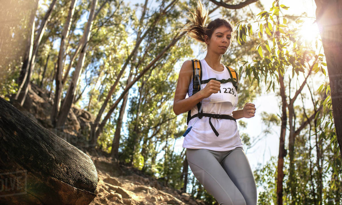 Fit young woman runner in sportswear running a mountain marathon with bright sunlight from the back. Fit trail runner running in a mountain race. Royalty-free stock photo