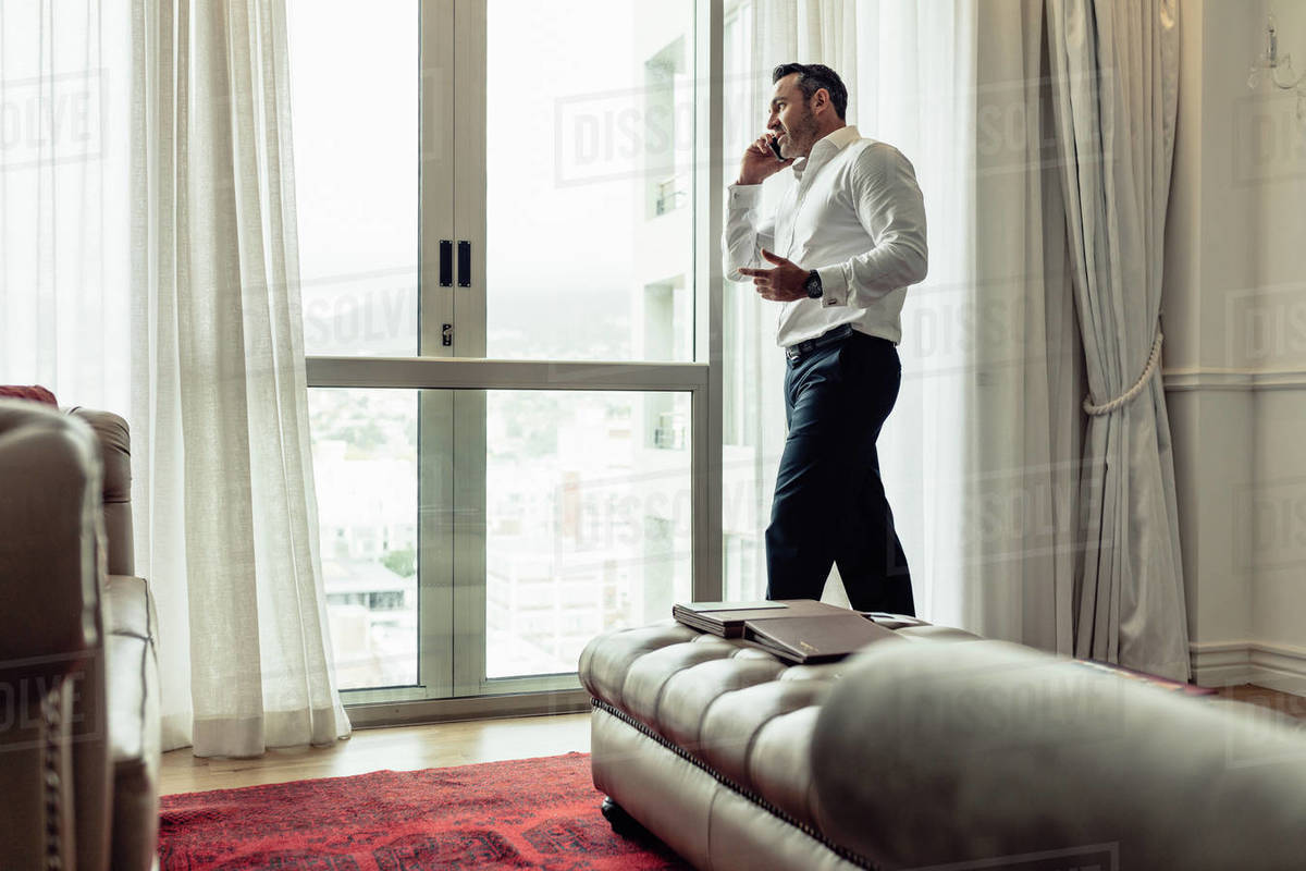 Businessman staying in hotel room and talking on mobile phone. CEO speaking on his cellphone in hotel room during business travel. Royalty-free stock photo