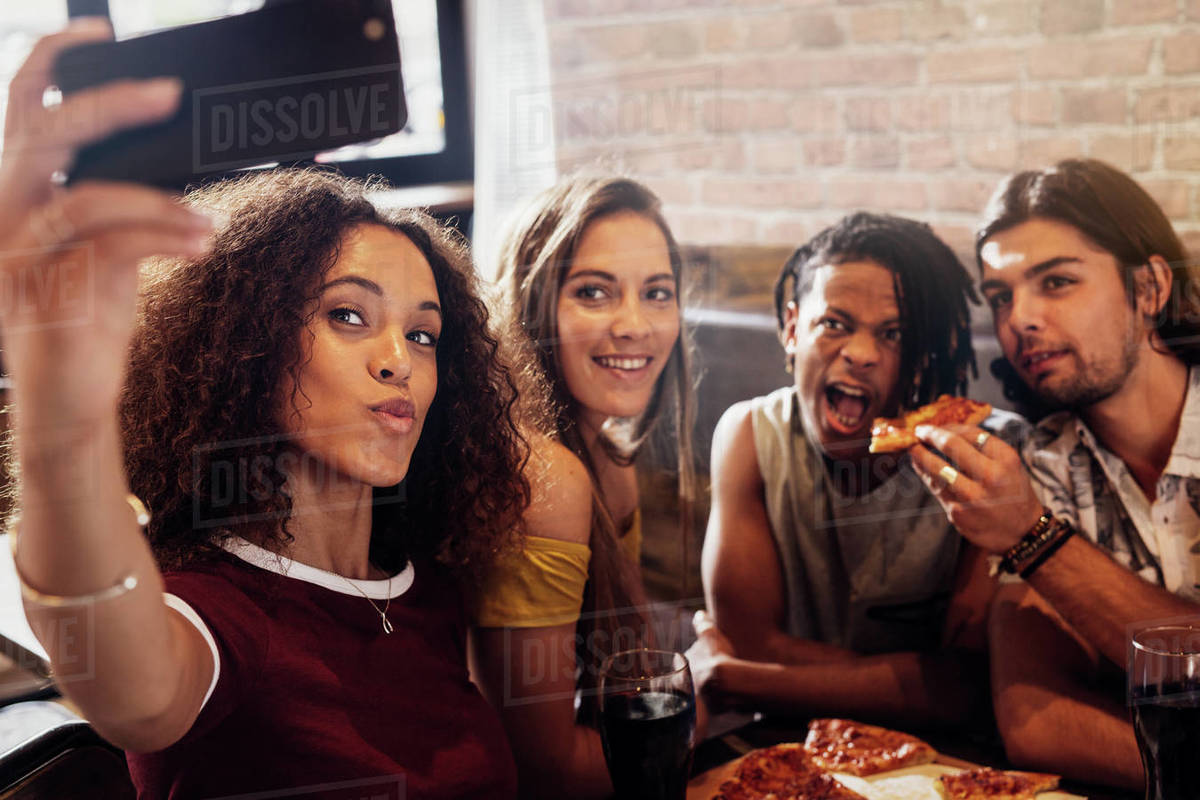 Woman taking selfie with friends eating pizza at a restaurant. Diverse group of men and women enjoying meal and taking selfie at restaurant. Royalty-free stock photo