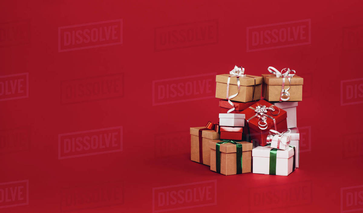Christmas Gift Box.Pile Of Christmas Gift Boxes Isolated On A Red Background Colorful Gift Boxes Tied With Ribbons And Bows Stock Photo