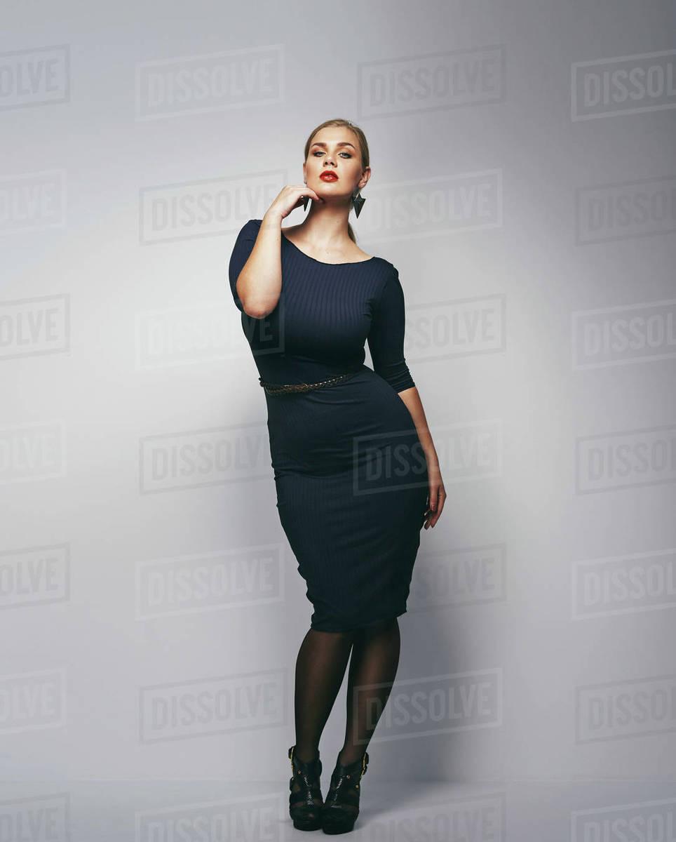Beautiful caucasian plus size secretary in dark blue dress. Full  D2012_41_025