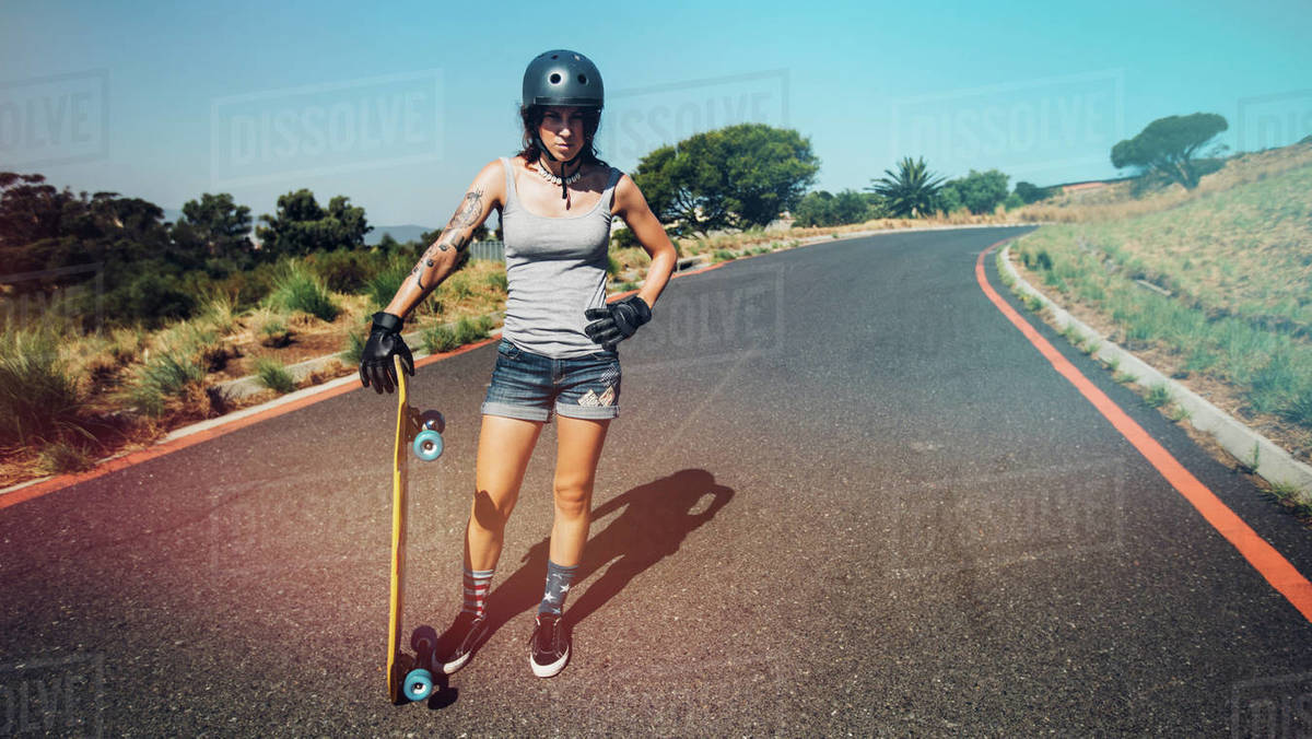 Full length portrait of young woman standing on a countryside highway with a longboard. Royalty-free stock photo