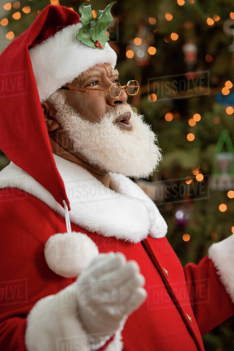 An African American man dressed as Santa Claus sitting in front of a Christmas tree laughing happily.  Royalty-free stock photo