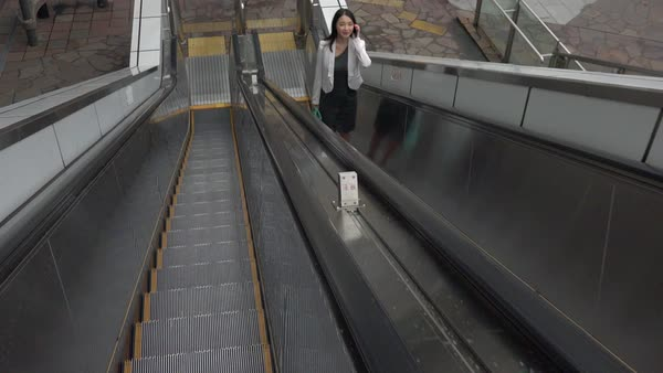 Happy beautiful Japanese female manager speaking on cell phone. Asian businesswoman, confident girl, busy woman talking with smartphone, mobile telephone on escalator in Tokyo Royalty-free stock video