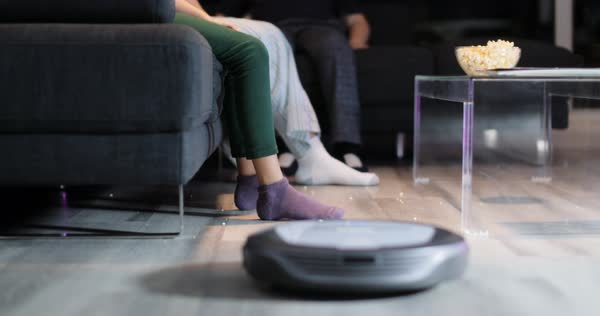 Family eating popcorn during movie night. Three persons, mother, daughter and kid watch television on sofa. They lift feet up when a round robot vacuum cleaner passes to clean the dirty floor. Royalty-free stock video