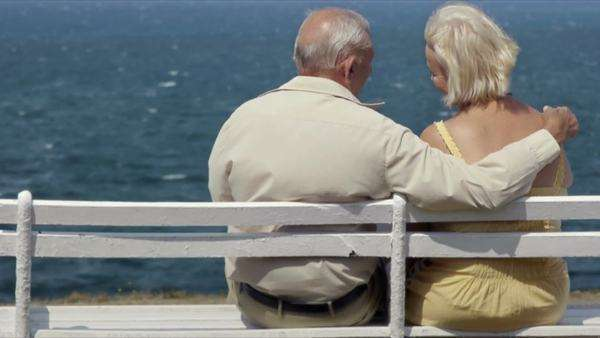 Elderly Caucasian couple sitting on a bench near the sea, hugging Royalty-free stock video