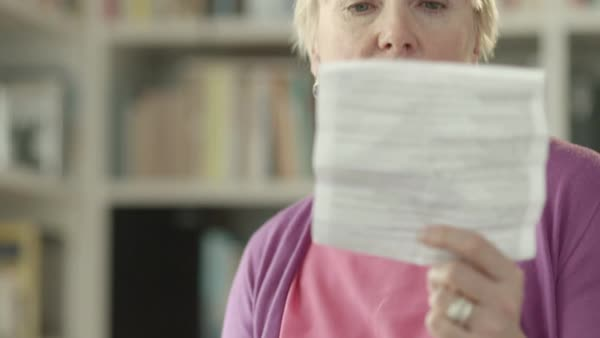 Elderly caucasian woman with medicine and reading drugs prescription. Old people and health care. Tilt shot Royalty-free stock video