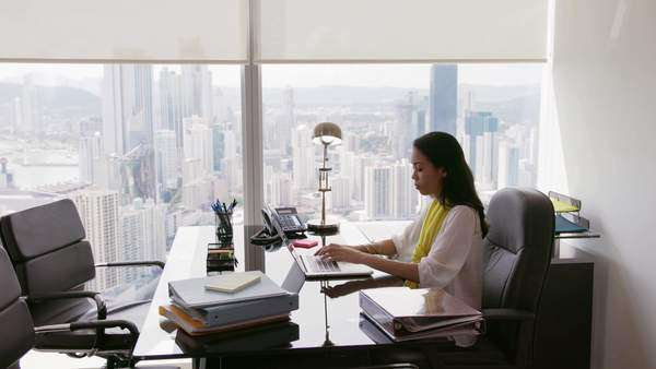adult businesswoman sitting in modern office with beautiful sight of the city the secretary writes