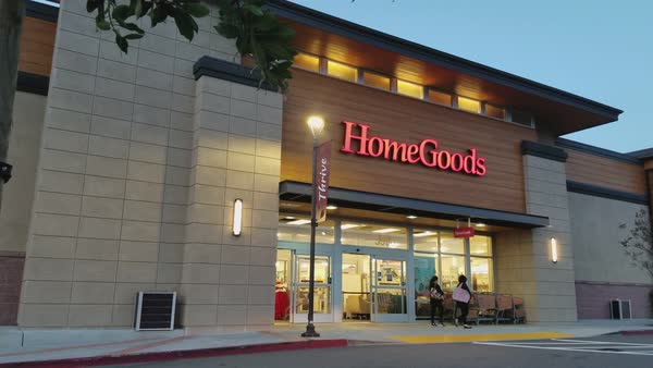 Facade Of Homegoods Home Furnishings Store At Night, With People Walking  Past And Cars Driving