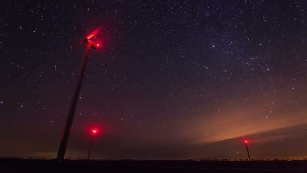 Wind turbines generating power at night timelapse with rotating starry sky on a background Royalty-free stock video