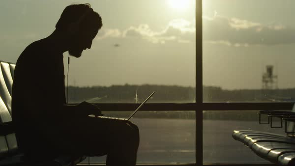 Silhouetted view a man listening to music and working on his laptop at an airport departure area Royalty-free stock video