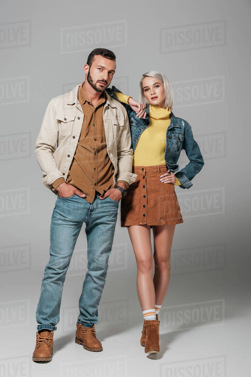 Couple of models posing in street style autumn outfit, on grey Royalty-free stock photo