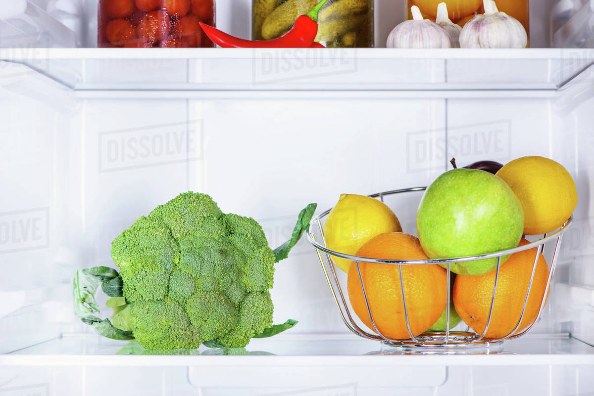 Broccoli And Ripe Tasty Fruits In Fridge Stock Photo Dissolve