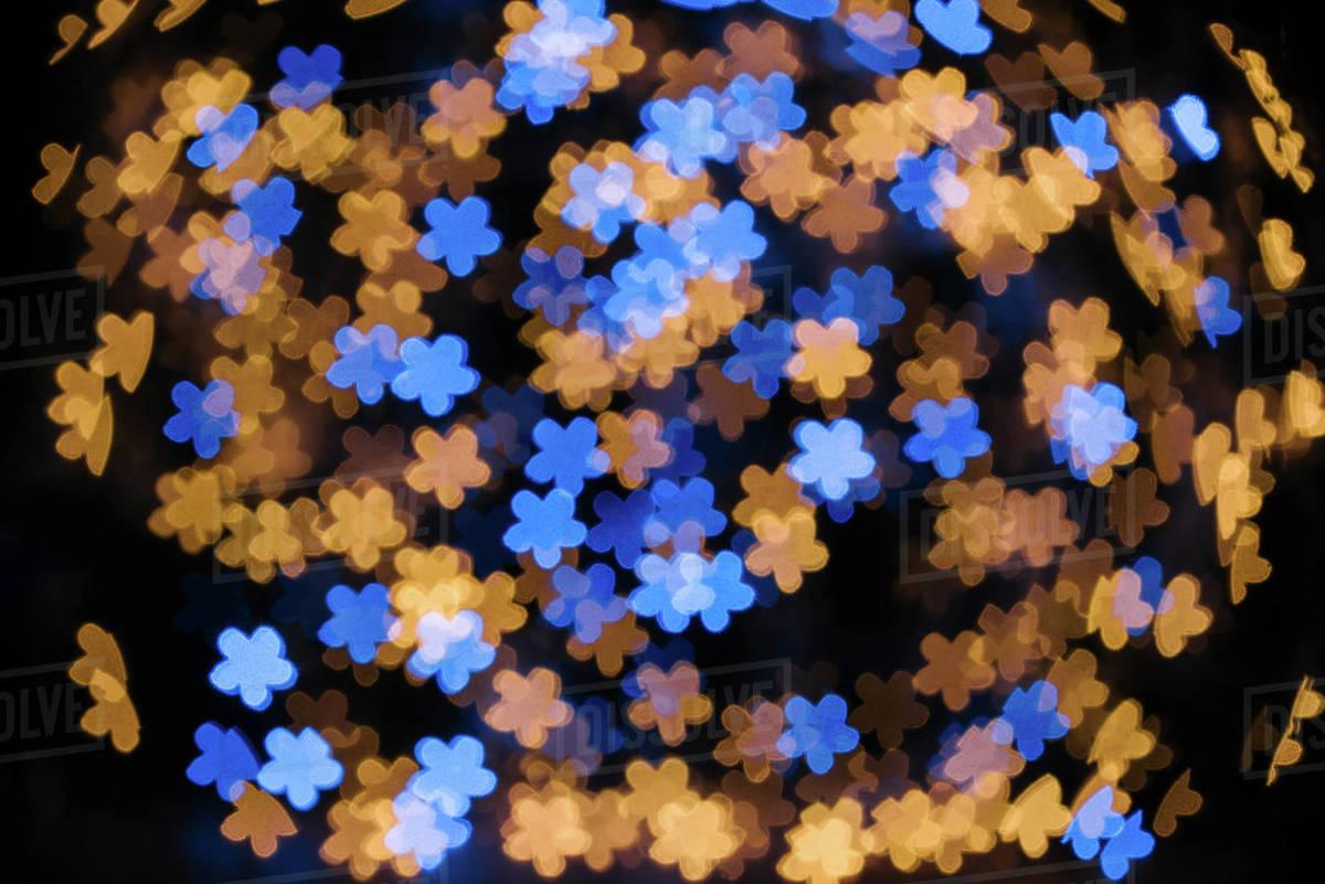 Full frame of shiny blue and golden stars bokeh lights on black backdrop  stock photo