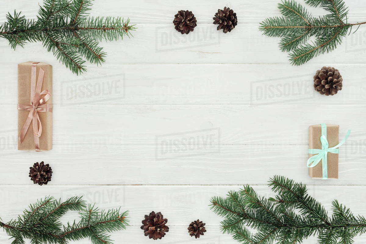 Christmas Top View.Top View Of Evergreen Coniferous Branches Pine Cones And Christmas Presents On White Wooden Background Stock Photo