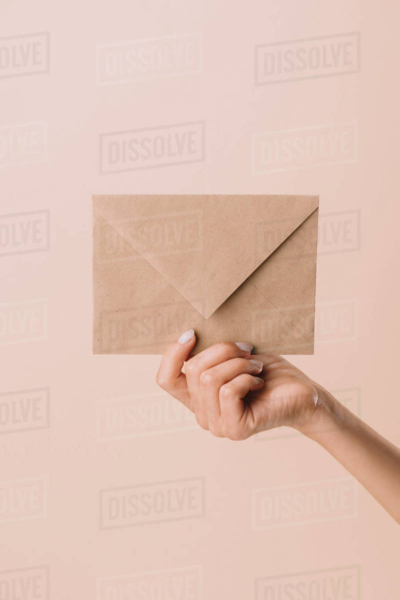 Cropped Shot Of Woman Holding Envelope Isolated On Beige Stock Photo Dissolve