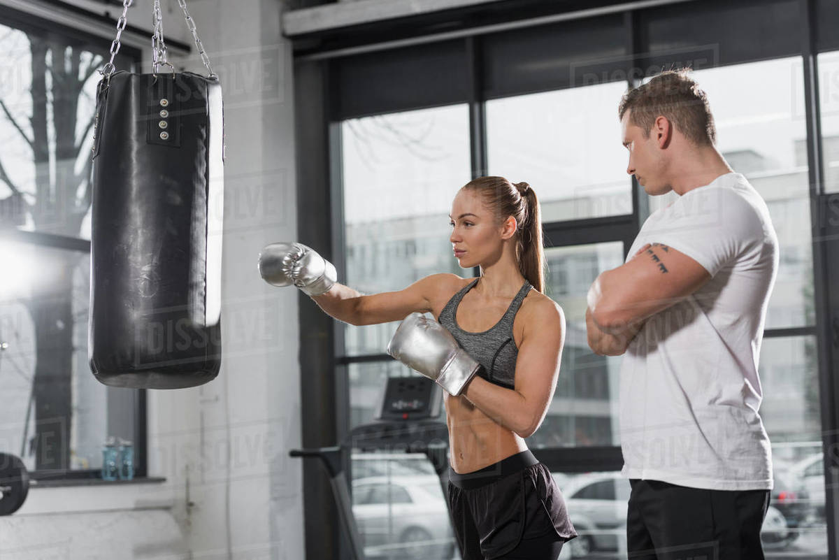 Handsome trainer watching how boxer training with punching bag in gym stock  photo