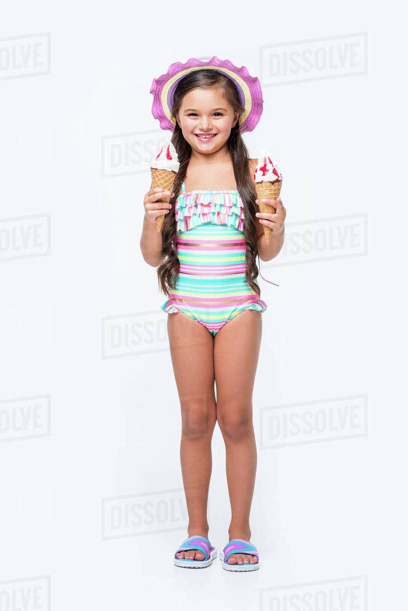 e009197451 Cute little girl in swimsuit holding ice cream and smiling at camera ...